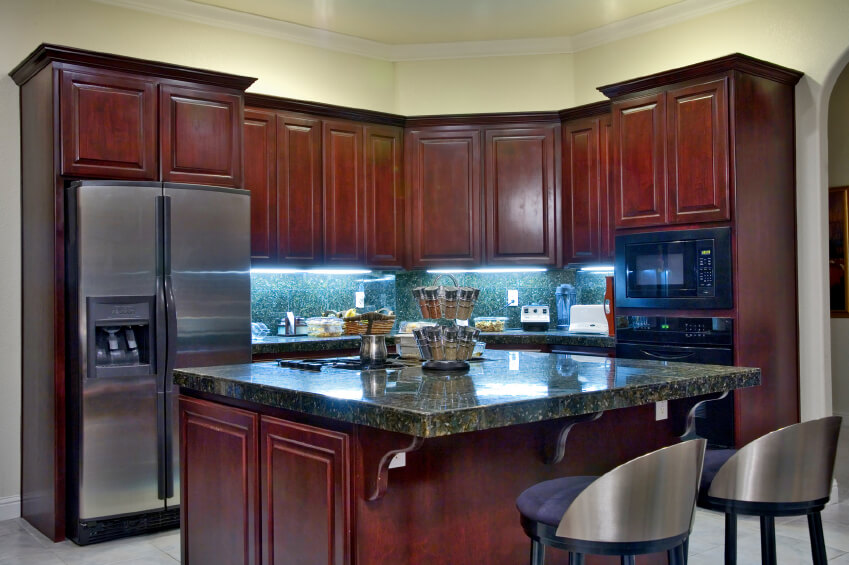 Awesome A small eat-in kitchen with rich cherry wood cabinets and stainless steel kitchen designs with islands for small kitchens