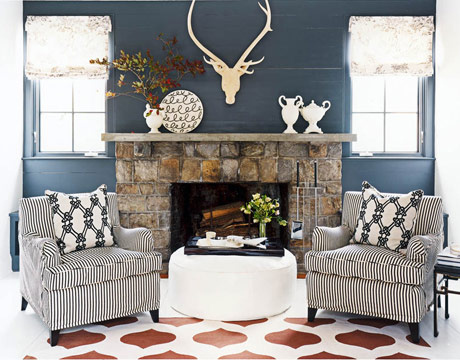 Stunning fireplace with matching chairs and a painted floor and a white ottoman with living room accessories
