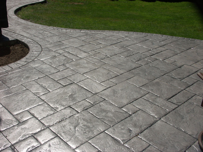 grey stamped concrete walkway in a backyard on a sunny day EDBJHTL