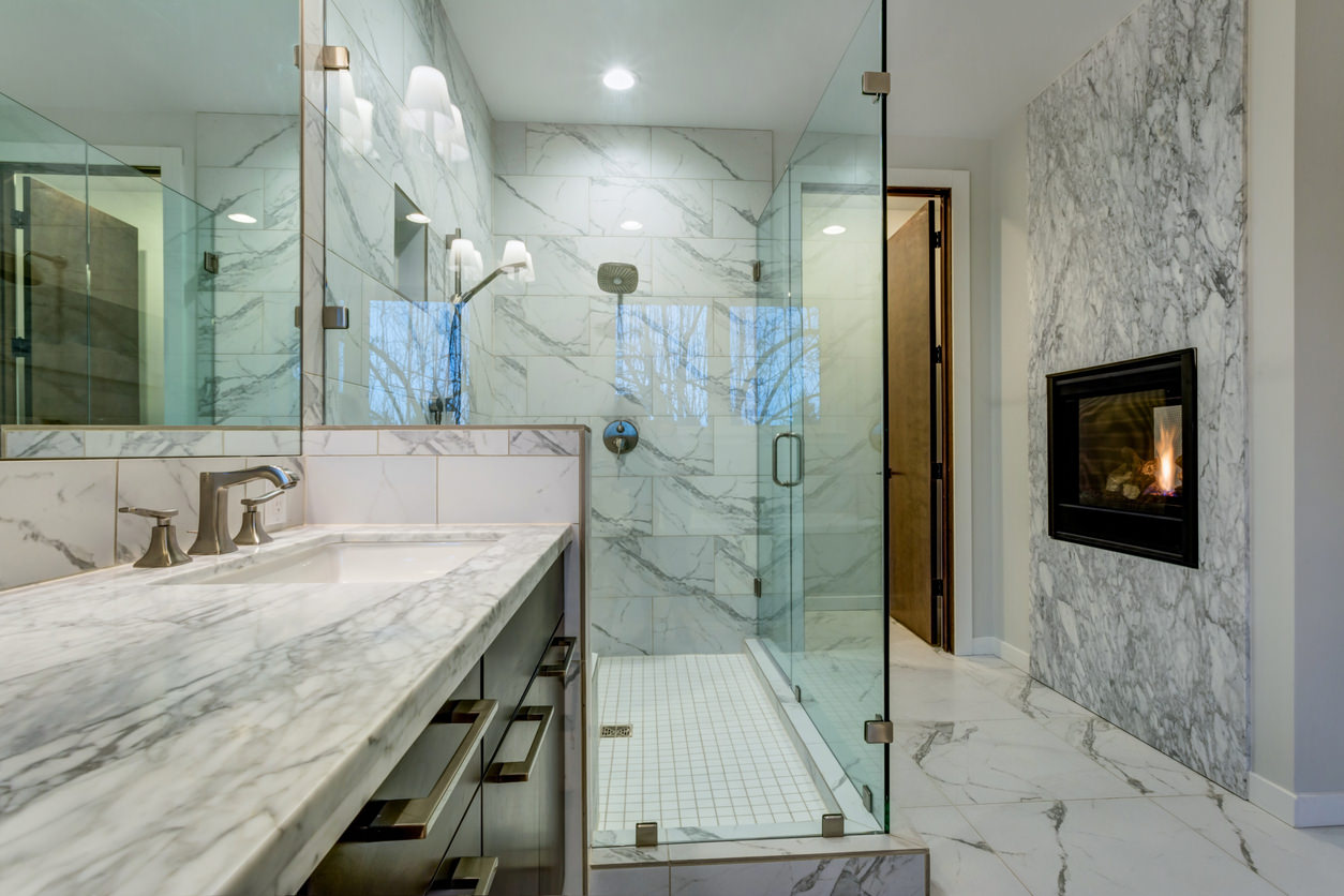 This beautiful marbled bathroom adds luxury with a mounted fireplace right  in the bathroom itself!