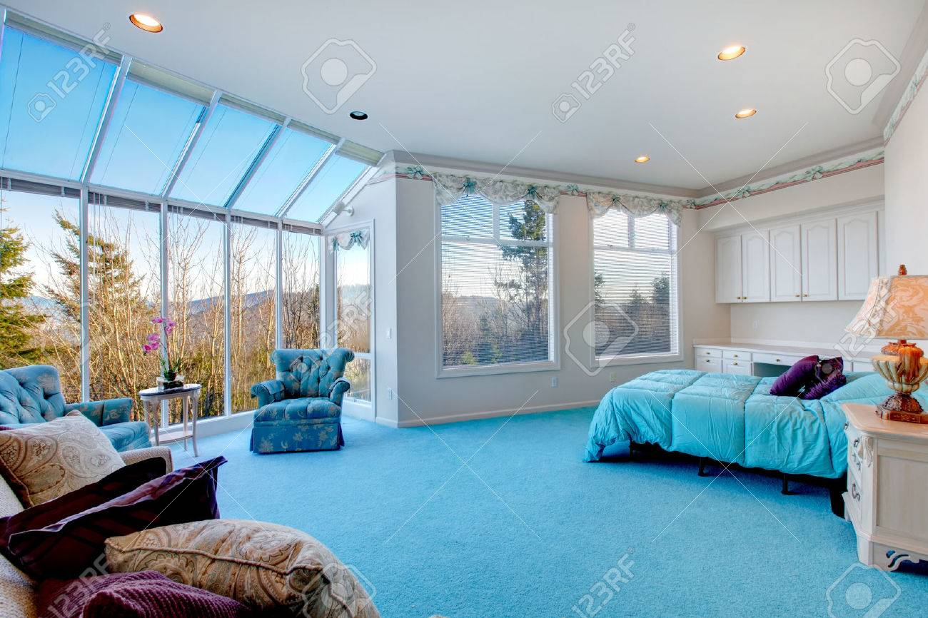 Great design for bedroom with glass wall. Blue carpet floor well matched  with light blue
