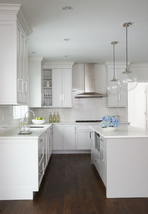 Beautiful kitchen features a pair of clear glass globe pendants