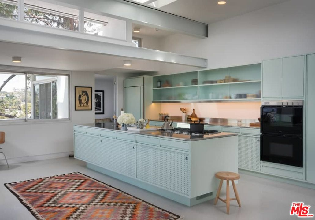 The home features a single wall kitchen with a large center island along  with seafoam-