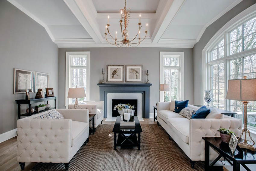 Beautiful living room with white furniture gray paint fireplace and  chandelier