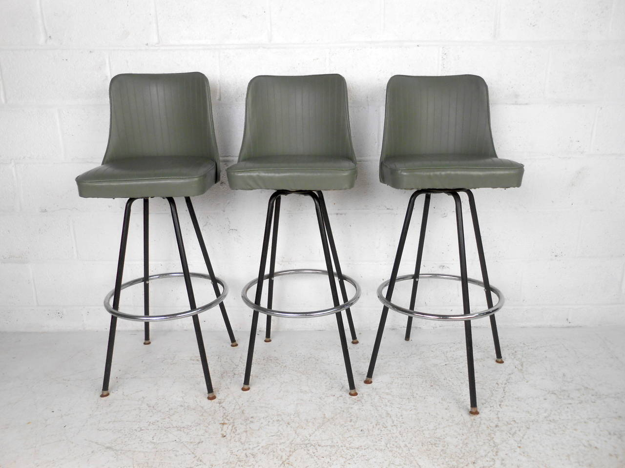 This set of three mid century bar stools by Atlas Specialty Manufacturing  feature a green vinyl