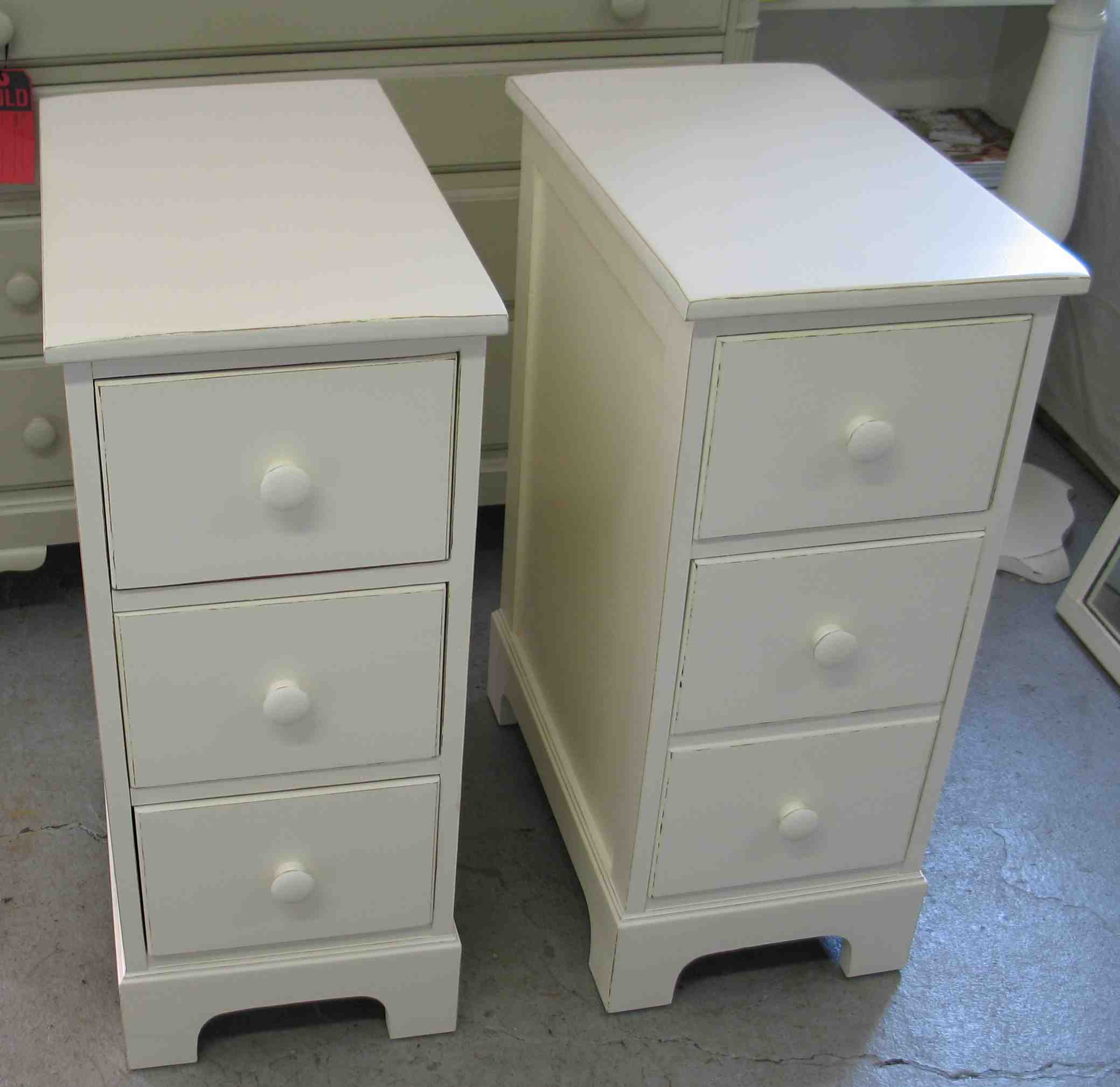 Bedroom. double white wooden Bedside Table having three drawer and white  knob also short.