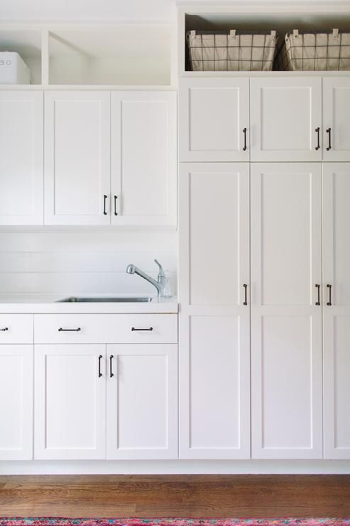 Amazing All white laundry room features white shaker cabinets adorned with oil  rubbed white cabinets for laundry room