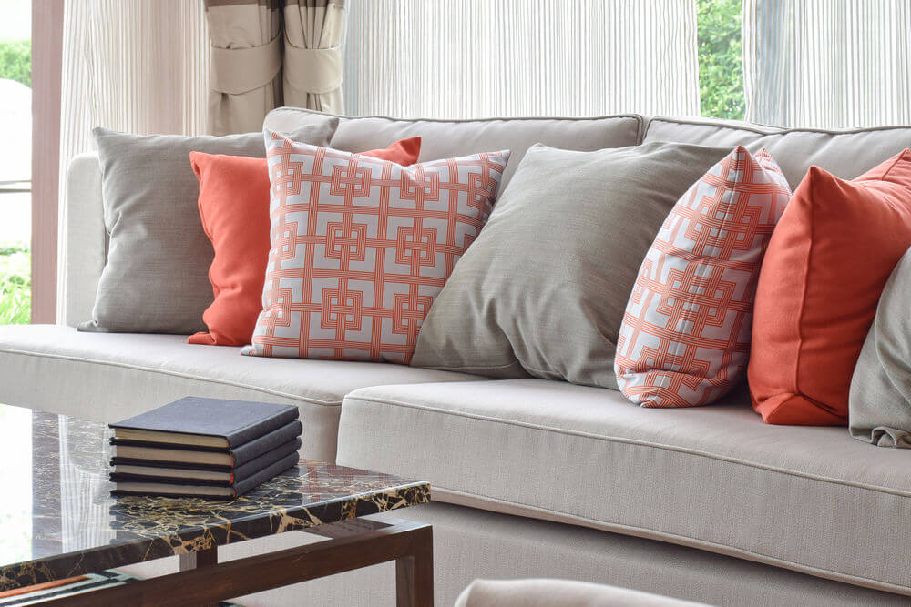 Unique Light grey sofa with a mix of bright orange and matching solid accent pillows for sofa