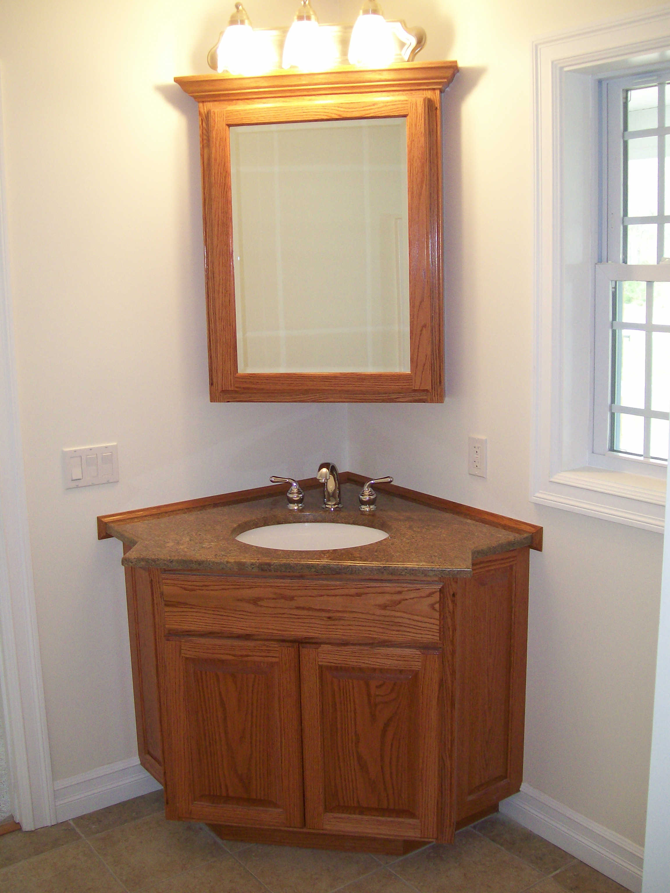 small bathroom corner vanity interior. round white wash basin in brown wooden bathroom vanity on BHHNROZ