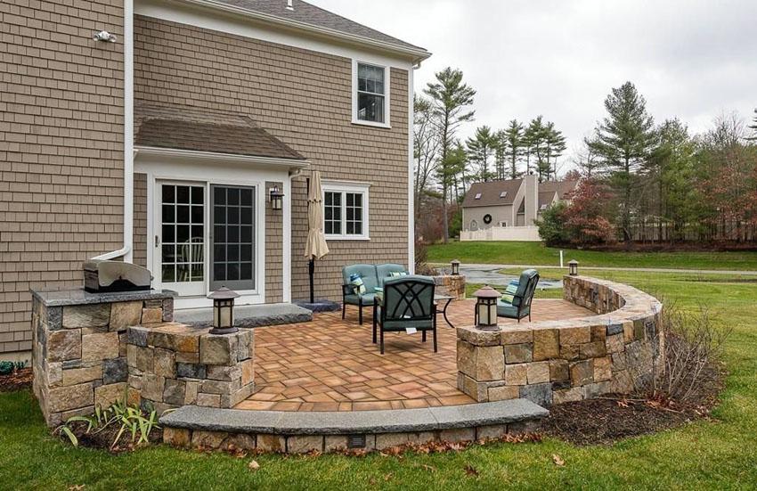stone patio ideas backyard raised stone patio with small wall and outdoor lighting ONRYZYN