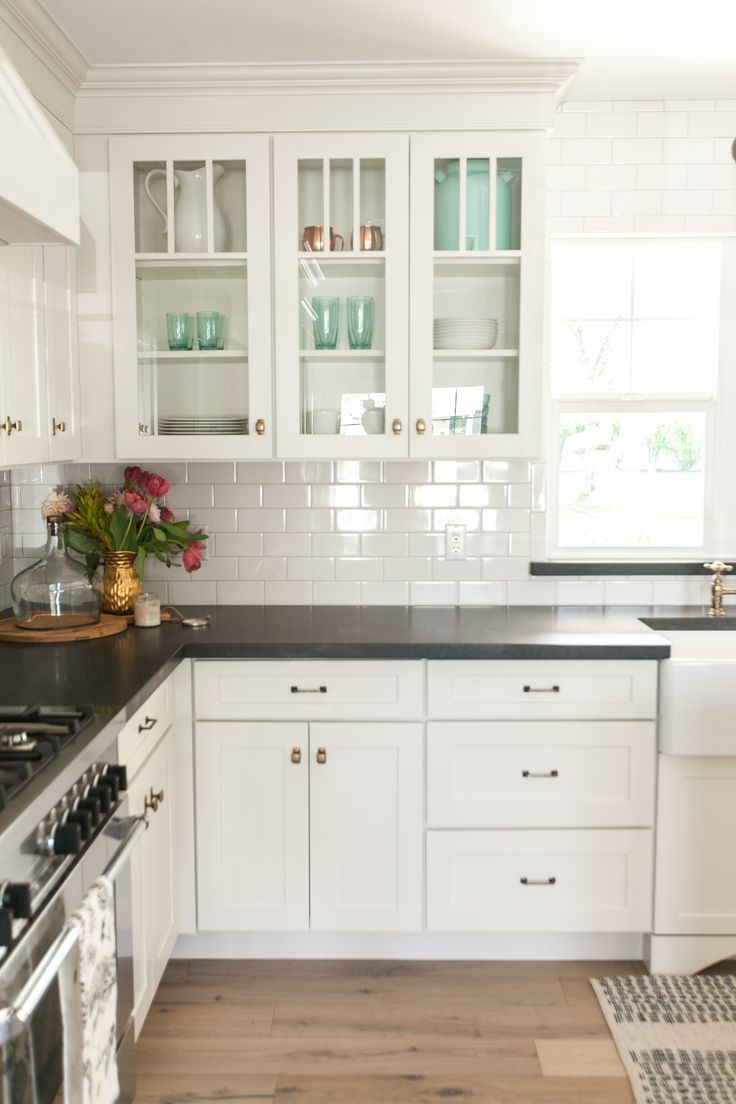 white kitchen cabinets, black countertops and white subway tile with white OBYDIPJ