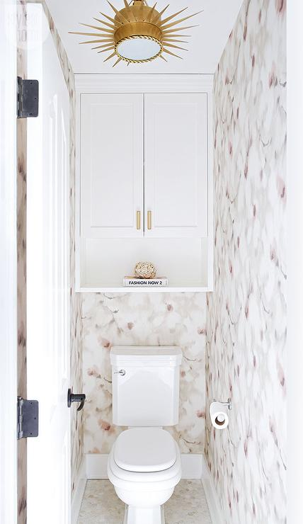 Chic water closet is clad in pink and gray floral wallpaper lined with  a cabinet and shelf hovering over a toilet illuminated by a Soleil Small  Pendant.