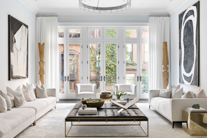 apartment with white walls, white couches, leather ottoman, and coffee  table book -