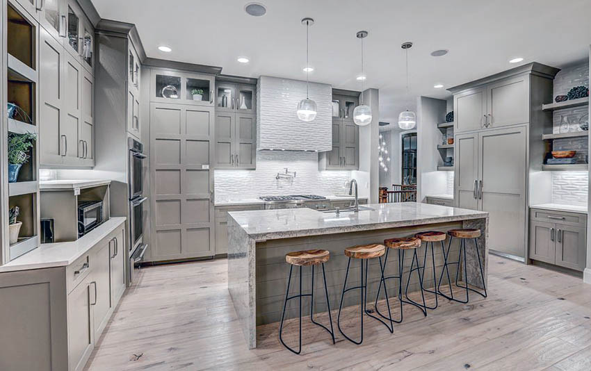 Contemporary kitchen with light gray cabinets, light wood floors and white  textured backsplash