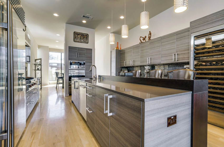 Contemporary kitchen with laminated cabinets and two level breakfast bar  and light wood floors