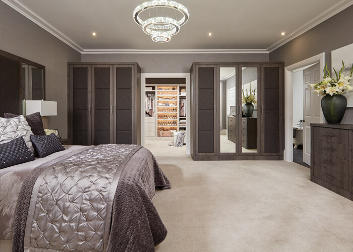 This bedroom features opulent, padded doors and headboards combined with  the warm, contemporary Anthracite Larch finish.