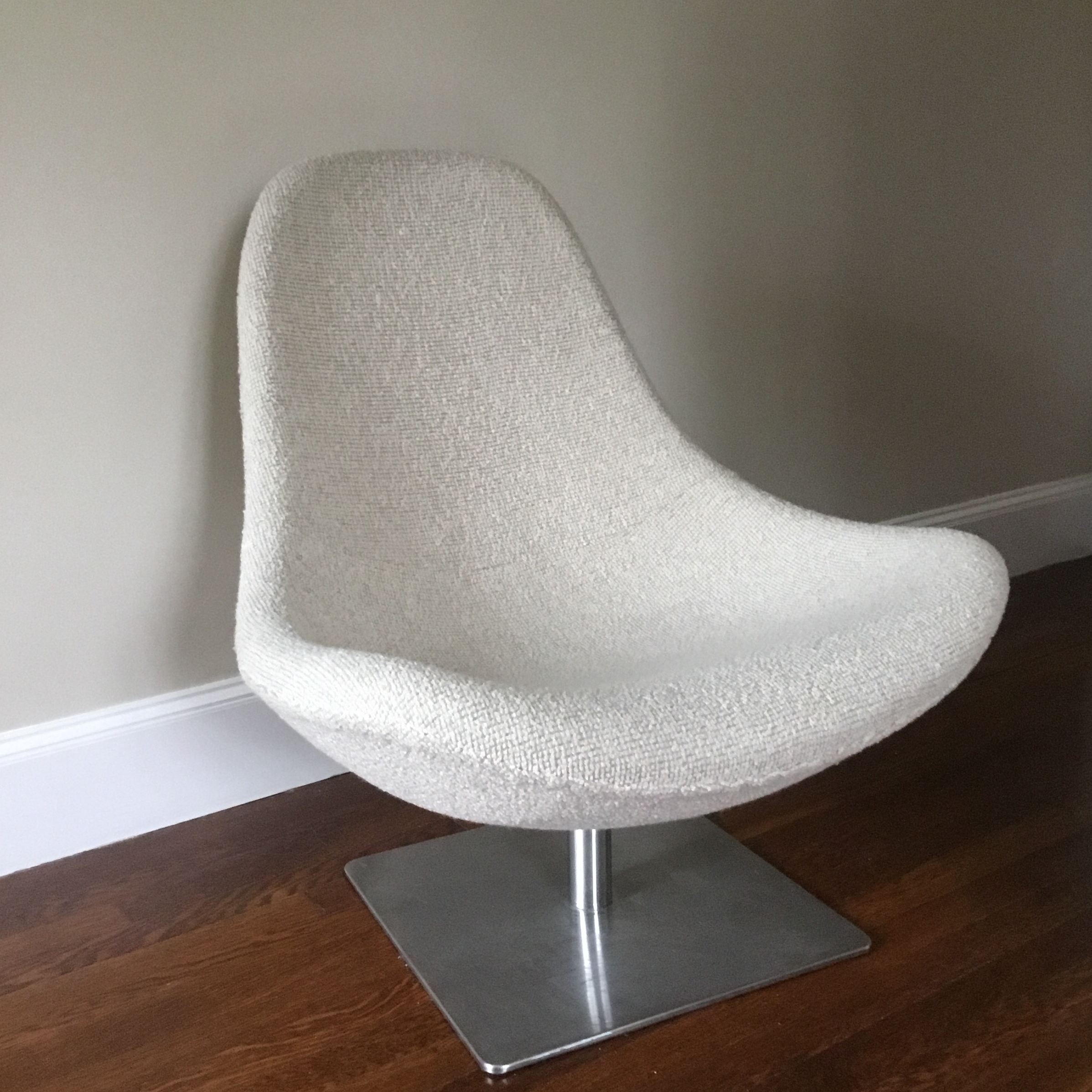 A cozy modern upholstered chair with a stainless steel swivel square base.  This new but. Anglo-Indian Mid Century Modern Swivel Lounge