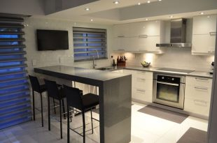 Small modern kitchen with gray quartz counter peninsula and white gloos  cabinets