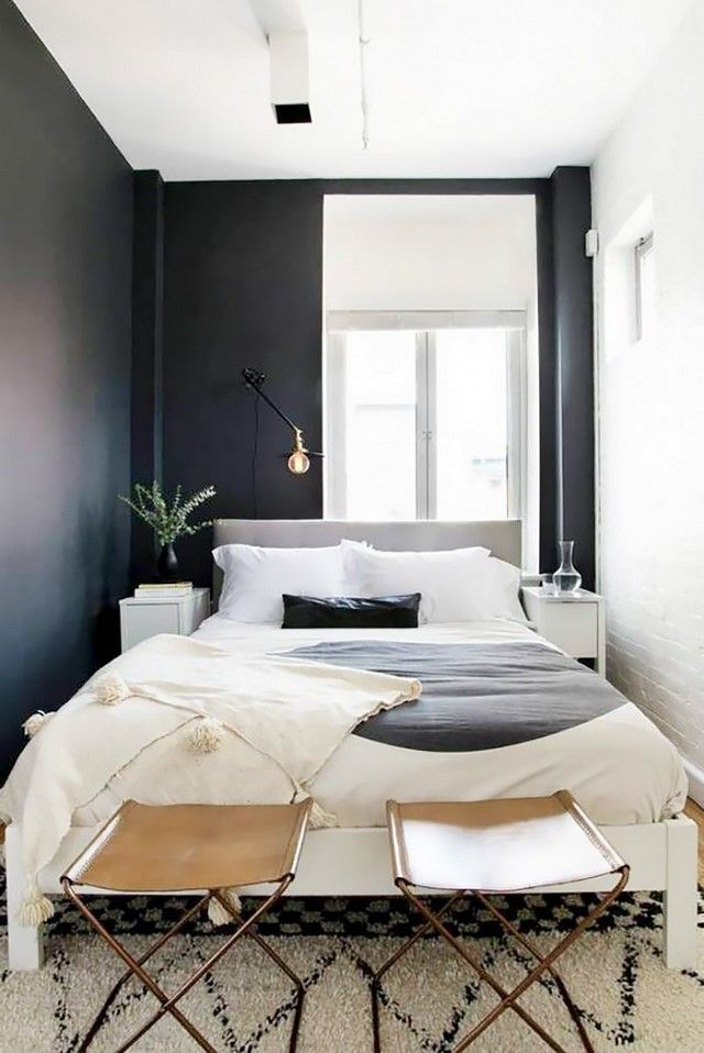 Small Swedish-inspired bedroom with black walls, simple bedding, and  leather stools