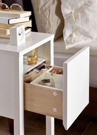 Close-up of small IKEA bedside table, drawer open to reveal inside storage.